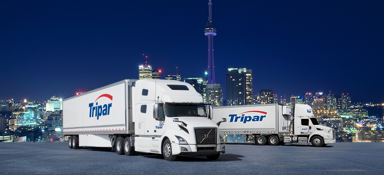 Two transport trucks with trailers in front of Toronto skyline