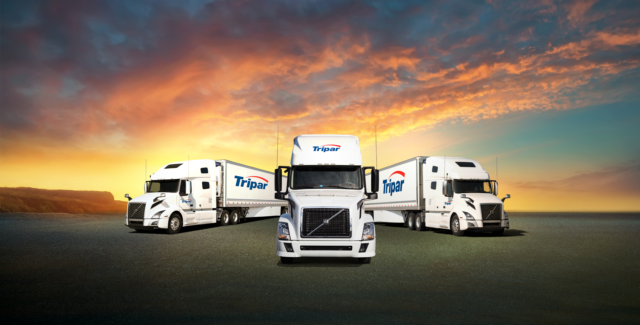 Three transport trucks and trailers parked with sunset in background